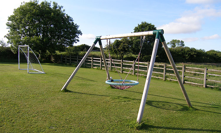 nest swing and football on grassed play area